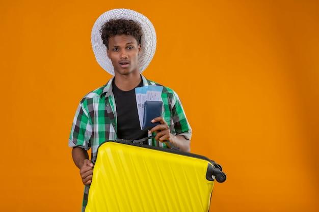 오렌지 배경 위에 만족 얼굴에 자신감이 미소로 카메라를보고 항공 티켓을 들고 가방으로 서 여름 모자에 젊은 아프리카 계 미국인 여행자 남자