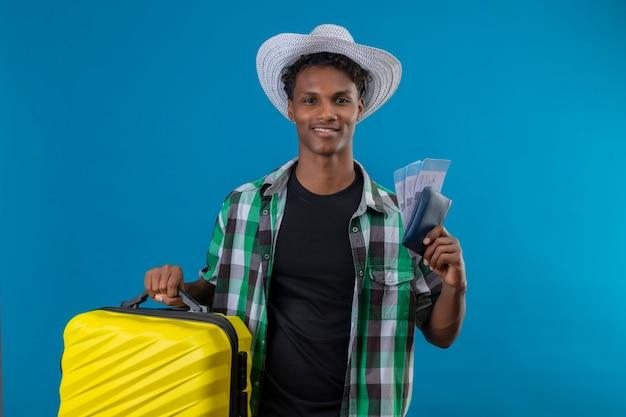 파란색 배경 위에 유쾌하게 긍정적이고 행복 미소 항공 티켓을 들고 가방으로 서 여름 모자에 젊은 아프리카 계 미국인 여행자 남자