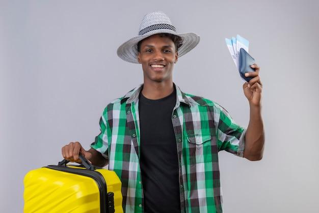 흰색 배경 위에 유쾌하게 긍정적이고 행복 미소 항공 티켓을 들고 가방으로 서 여름 모자에 젊은 아프리카 계 미국인 여행자 남자