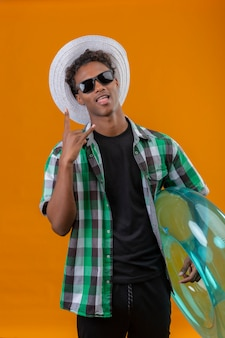 オレンジ色の背中にカメラ立って見て楽しい舌を突き出してロックサインをやっているインフレータブルリングを保持している黒いサングラスをかけている夏帽子の若いアフリカ系アメリカ人旅行者男