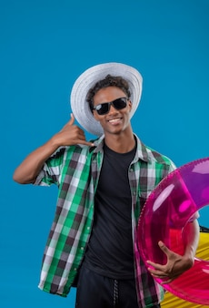 Молодой афро-американский путешественник в летней шляпе, одетый в черные солнцезащитные очки, держит надувное кольцо, весело улыбаясь, делая жест «позвони мне», стоя на синем фоне