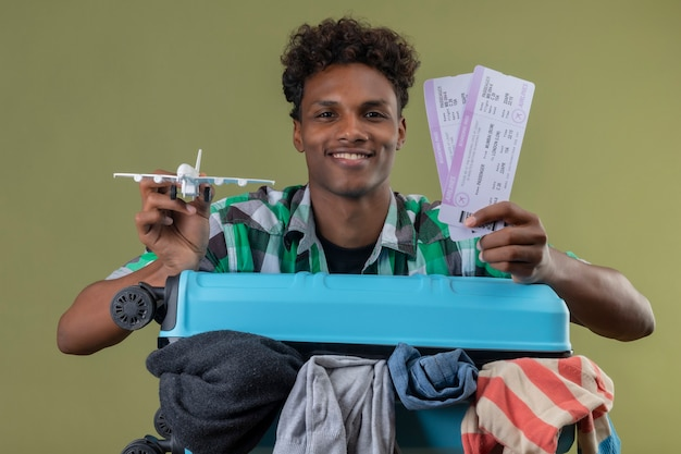 Young african american traveler man standing with suitcase full of clothes holding air tickets and toy air plane looking at camera smiling happy and positive over green background