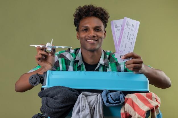 Молодой афро-американский путешественник, стоящий с чемоданом, полным одежды, держит авиабилеты и игрушечный самолет, глядя в камеру, улыбаясь счастливым и позитивным на зеленом фоне