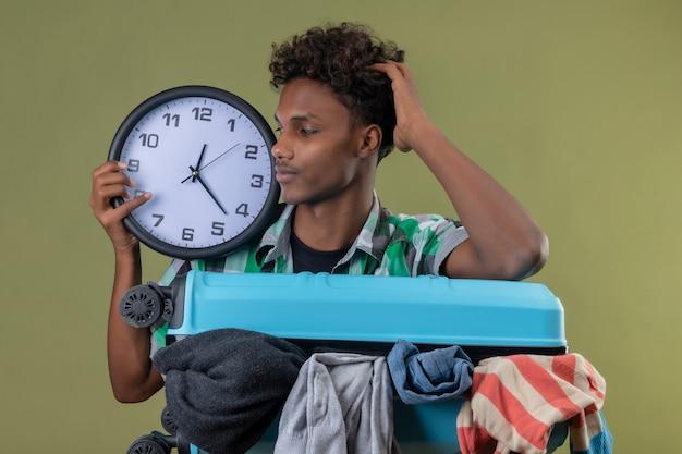 緑の背景の上の顔に困惑した表情でそれを見て時計を保持している服の完全なスーツケースを持って立っている若いアフリカ系アメリカ人旅行者男