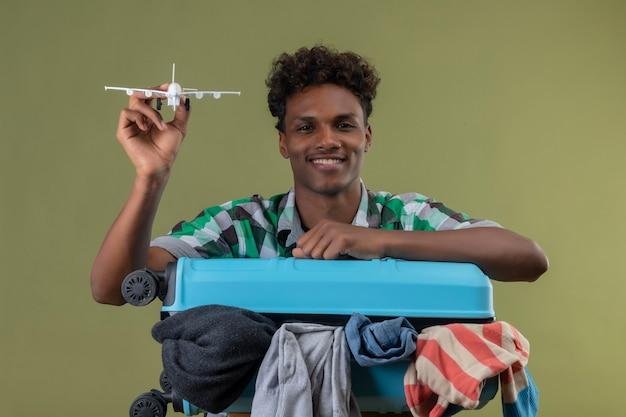 緑の背景で元気に笑顔のカメラを見ておもちゃの飛行機を保持している服の完全なスーツケースを持って立っている若いアフリカ系アメリカ人旅行者男
