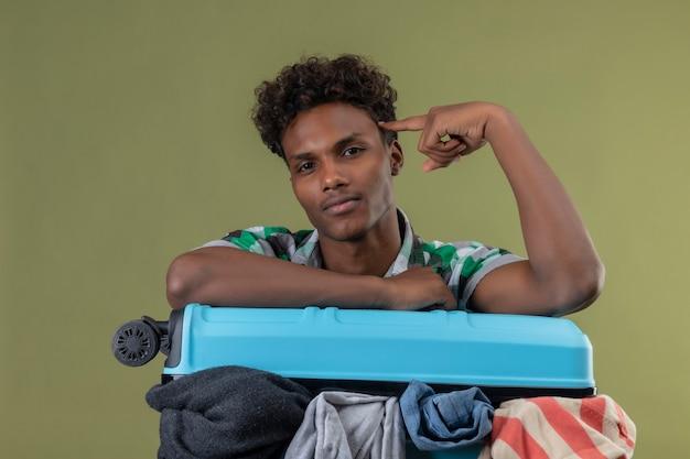 緑の背景の上のタスクに焦点を当てて自信を持って探している寺院を指している服の完全なスーツケースを持って立っている若いアフリカ系アメリカ人旅行者男