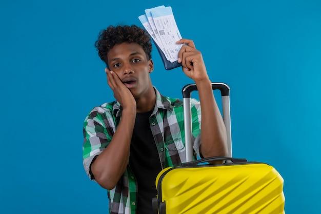 파란색 배경 위에 놀란 카메라를보고 항공 티켓을 들고 가방으로 서 젊은 아프리카 계 미국인 여행자 남자