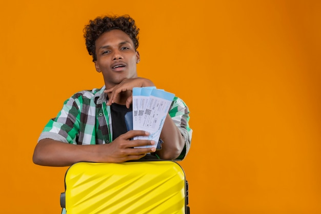 Young african american traveler man standing with suitcase holding air tickets looking at camera with confident smile on face satisfied over orange background