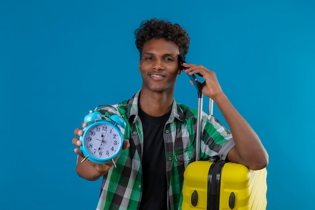 Young african american traveler man standing with suitcase holding alarm clock showing to camera smiling confident while talking on mobile phone over blue background