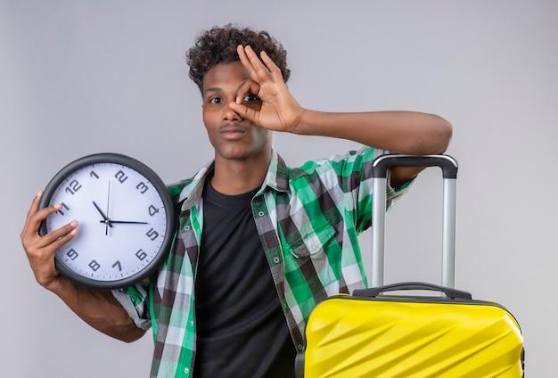 Молодой афро-американский путешественник, стоящий с чемоданом, держит часы, делает хорошо знаком, глядя в камеру через этот знак, улыбаясь позитивно и счастливо на белом фоне