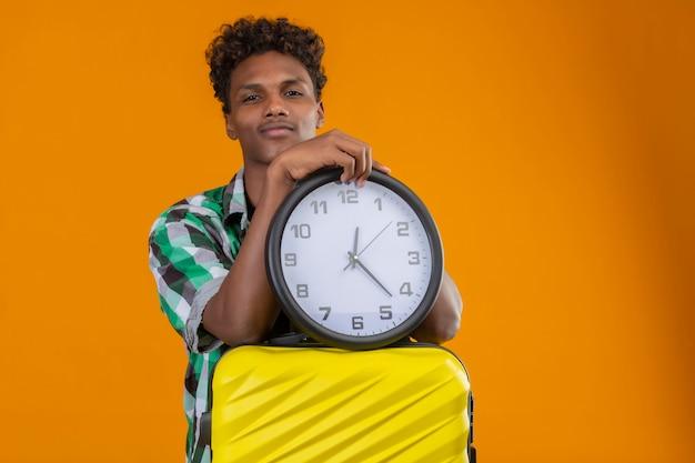 Молодой афро-американский путешественник, стоящий с чемоданом, держит часы и смотрит в камеру с уверенной улыбкой на лице на оранжевом фоне