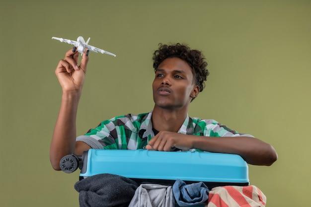 緑の背景の上の顔に真剣な自信のある表情でそれを見ておもちゃの飛行機を保持しているスーツケースを持って立っている若いアフリカ系アメリカ人旅行者男