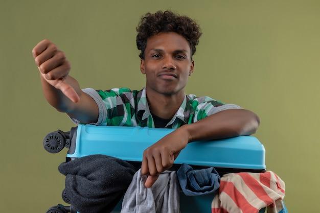 Молодой афро-американский путешественник, стоящий с чемоданом, недовольно смотрит в камеру, показывает палец вниз на зеленом фоне