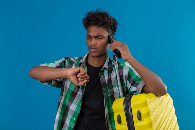 青い背景の上に携帯電話で話している間時間を思い出させる隠された手を見てスーツケースを持って立っている若いアフリカ系アメリカ人旅行者男