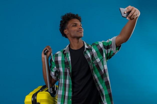 Молодой афро-американский путешественник, стоящий с чемоданом, делает селфи, используя свой смартфон, стоящий на синем фоне