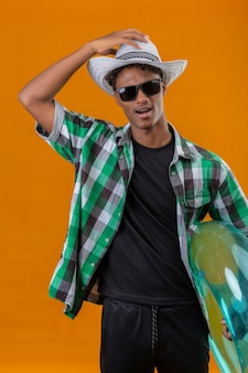 Young african american traveler man in summer hat wearing black sunglasses holding inflatable ring exited looking at camera touching his hat standing over orange background