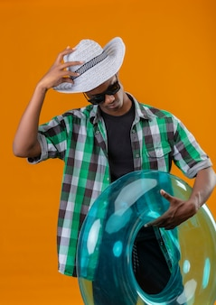 Young african american traveler man in summer hat wearing black sunglasses holding inflatable ring looking down touching his hat standing over orange background