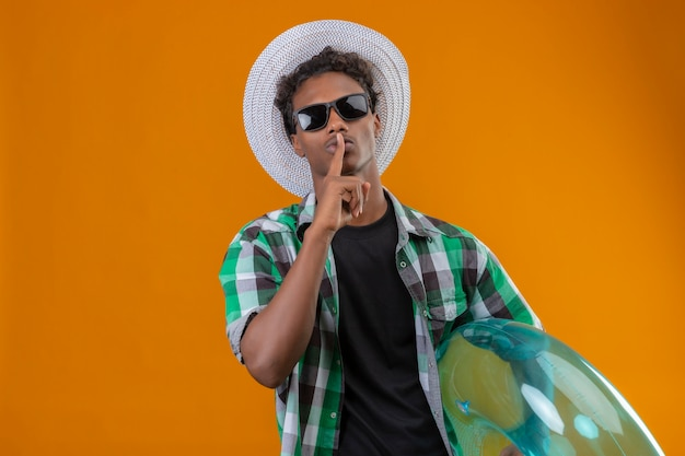 Young african american traveler man in summer hat wearing black sunglasses holding inflatable ring making silence gesture with finger on lips standing over orange background
