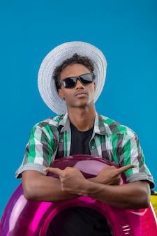 Uomo giovane viaggiatore afroamericano in cappello estivo indossando occhiali da sole neri che tiene anello gonfiabile in piedi con le mani incrociate che punta ai lati con le dita in piedi su sfondo blu