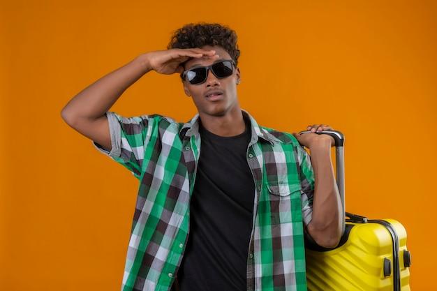 Uomo giovane viaggiatore afroamericano che indossa occhiali da sole neri che tiene la valigia che guarda lontano con la mano sulla testa per guardare qualcuno o qualcosa in piedi su sfondo arancione