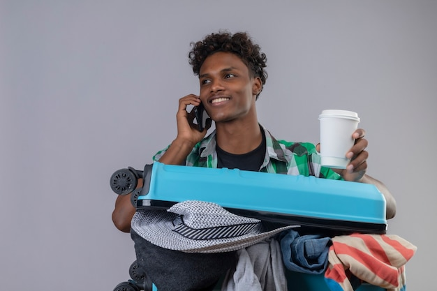 Young african american traveler man with suitcase full of clothes holding cup of coffee while talking on mobile phone smiling with happy face standing over white background