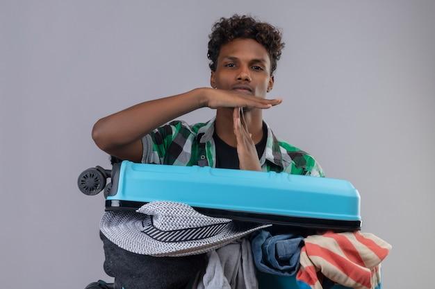 Uomo giovane viaggiatore afroamericano con la valigia piena di vestiti che guarda l'obbiettivo facendo segno di time out con le mani con espressione seria sul viso in piedi su sfondo bianco