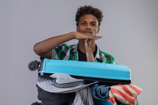 Uomo giovane viaggiatore afroamericano con la valigia piena di vestiti che guarda l'obbiettivo facendo segno di time out con le mani con espressione seria sul viso