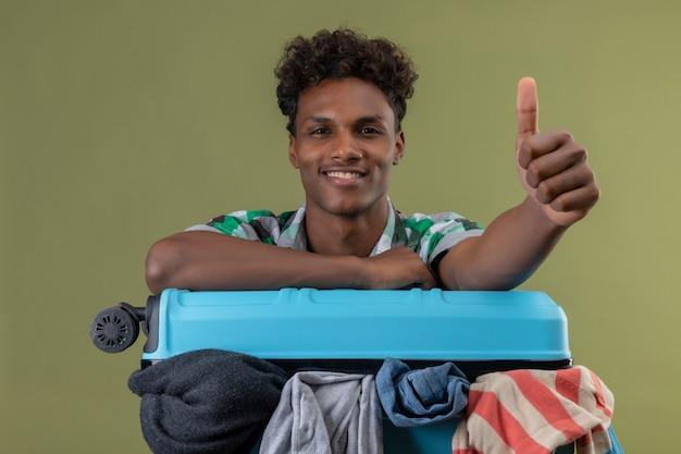 Uomo giovane viaggiatore afroamericano con la valigia piena di vestiti che guarda l'obbiettivo sorridente allegramente, positivo e felice, mostrando pollice in alto su sfondo verde