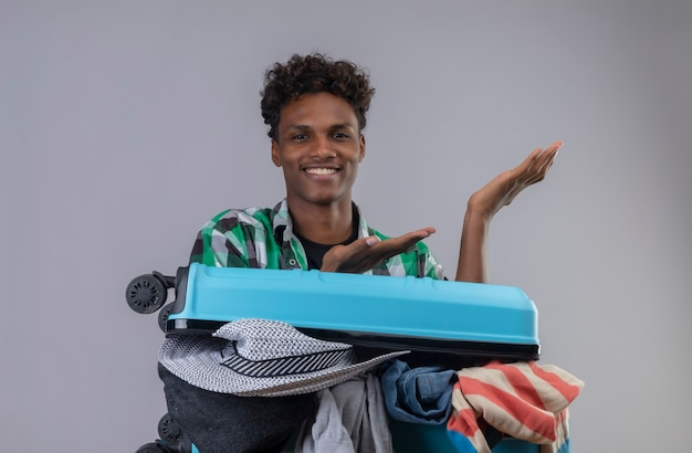 Uomo giovane viaggiatore afroamericano con la valigia piena di vestiti che guarda l'obbiettivo che sorride allegramente presentando con le braccia delle sue mani
