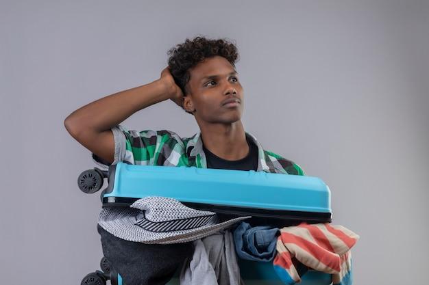 Uomo giovane viaggiatore afroamericano con la valigia piena di vestiti con la mano sulla testa che osserva da parte con espressione pensierosa