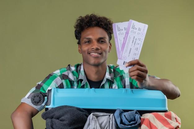 녹색 배경 위에 유쾌하고 긍정적이고 행복한 미소를 카메라를보고 항공 티켓을 들고 옷으로 가득한 가방을 가진 젊은 아프리카 계 미국인 여행자 남자