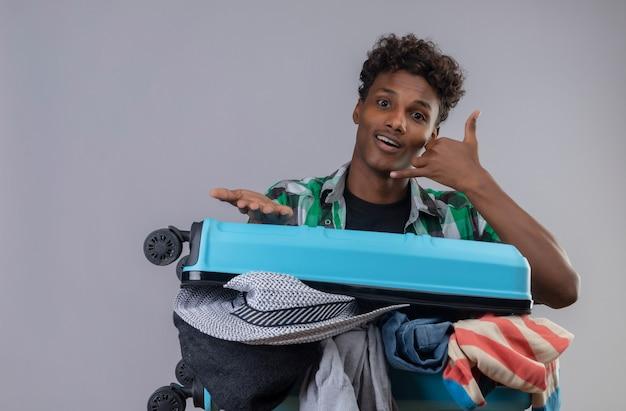 Молодой афро-американский путешественник с чемоданом, полным одежды, делает жест, называя меня, с удивленной рукой, стоящей на белом фоне