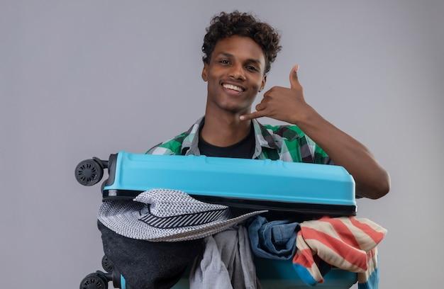 白い背景の上に元気に立って笑顔の手でジェスチャーをかける服の完全なスーツケースを持つ若いアフリカ系アメリカ人旅行者男