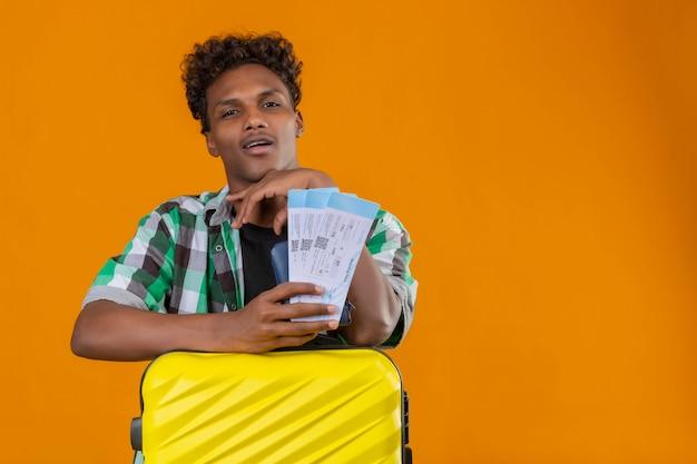 오렌지 배경 위에 만족 얼굴에 자신감 미소로 카메라를보고 항공 티켓을 들고 가방을 가진 젊은 아프리카 계 미국인 여행자 남자,