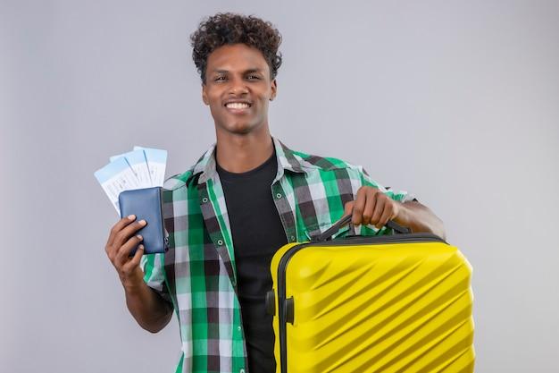 Uomo giovane viaggiatore afroamericano con la valigia che tiene i biglietti aerei sorridendo allegramente, positivo e felice