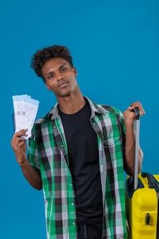 얼굴에 자신감이 미소로 항공 티켓을 들고 가방을 가진 젊은 아프리카 계 미국인 여행자 남자, 만족
