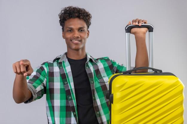 Uomo giovane viaggiatore afroamericano con la valigia che punta alla telecamera, sorridente fiducioso