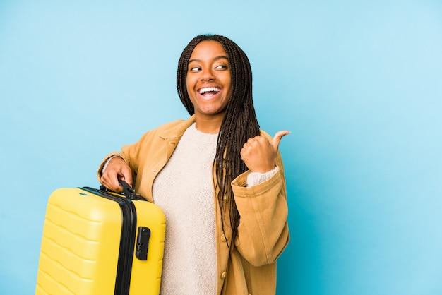 Молодая афро-американская женщина путешественника, держащая чемодан, изолировала точки с большим пальцем, смеясь и беззаботно.