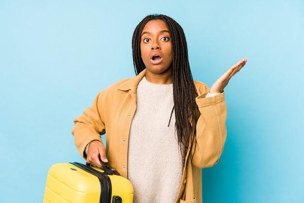 Молодая афро-американская женщина путешественника, держащая изолированный чемодан, удивлена и потрясена.