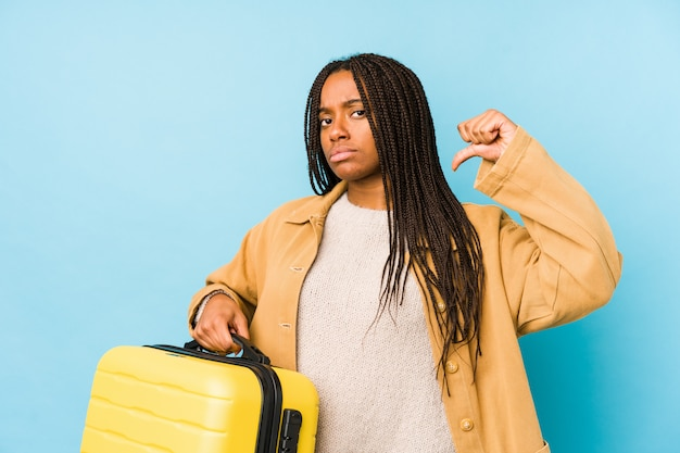 Young african american traveler woman holding a suitcase isolated feels proud and self confident, example to follow.