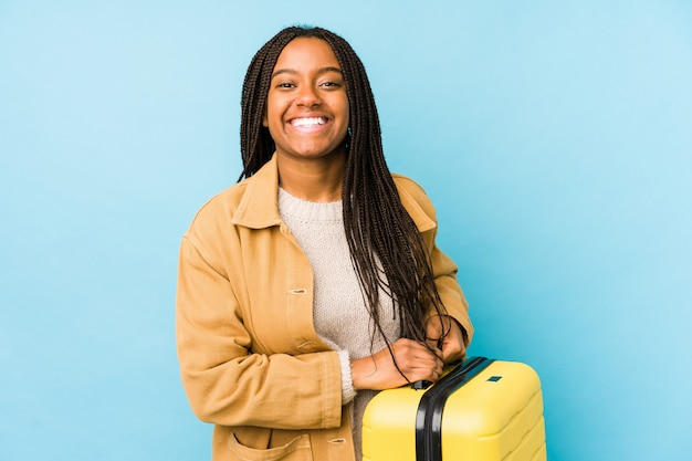Young african american traveler woman holding a suitcase isolated laughing and having fun.
