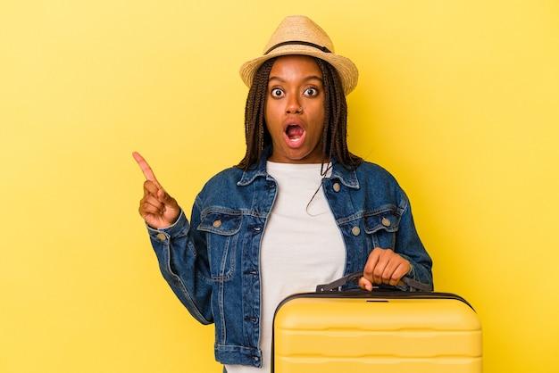 Молодой афро-американский путешественник женщина держит чемодан, изолированные на желтом фоне, указывая в сторону