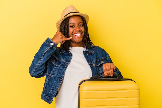 Young african american traveler woman holding suitcase isolated on yellow background  showing a mobile phone call gesture with fingers.