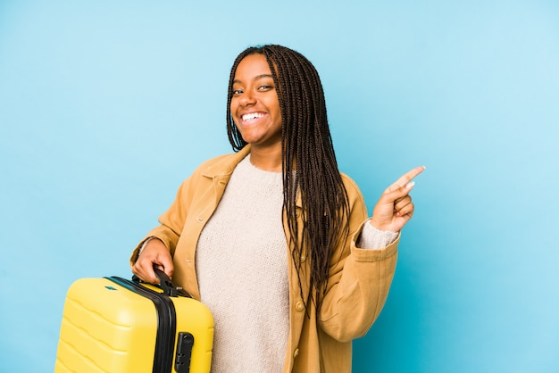 Young african american traveler woman holding a suitcase smiling and pointing aside, showing something at blank space.