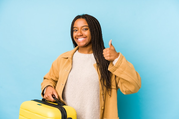 Young african american traveler woman holding a suitcase smiling and raising thumb up