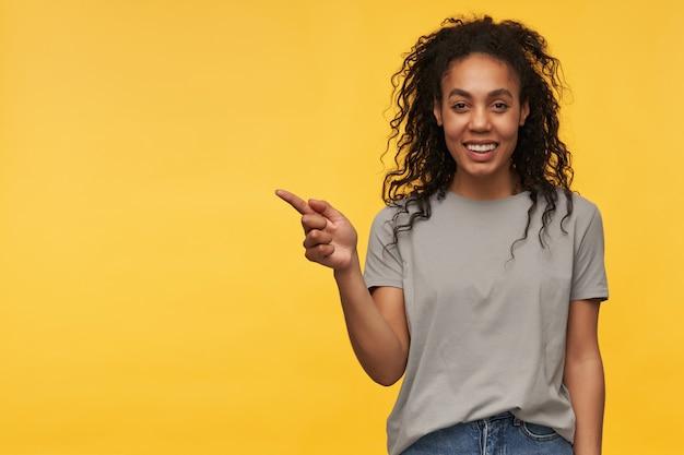 若いアフリカ系アメリカ人はグレーの t シャツを着て、指でコピー スペースを指さし、ポジティブな表情で広く笑う