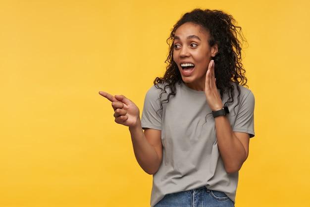 젊은 아프리카 계 미국인은 회색 티셔츠를 입고 손가락으로 복사 공간을 가리키며 긍정적 인 표정으로 넓게 미소 짓습니다.