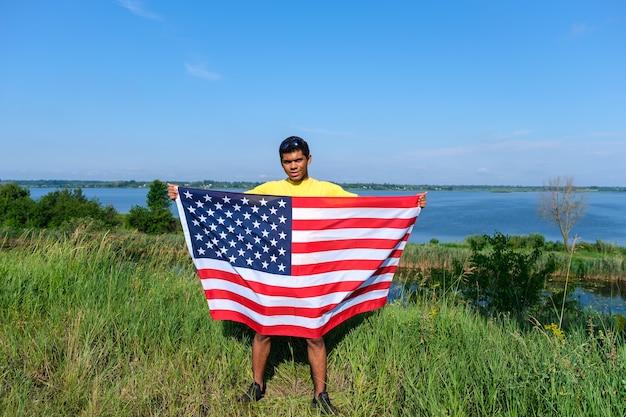 화창한 여름에 강 옆에 미국 국기가 서 있는 젊은 아프리카계 미국인