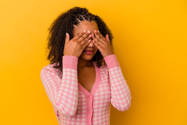 Young african american woman  afraid covering eyes with hands.