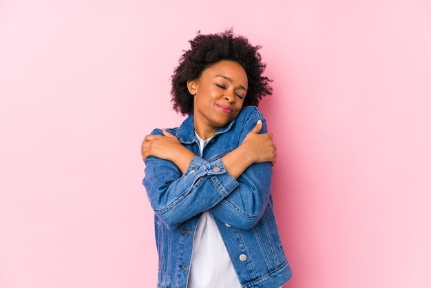 Молодая афро-американская женщина против розового фона изолировала объятия, беззаботно улыбаясь и счастливо.